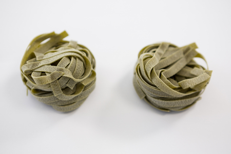 carbohydrates: Roll of tagliatelle pasta on white background