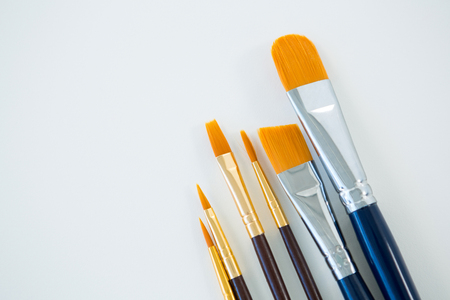 Various dirty paintbrushes arranged in a row on white background Stock Photo