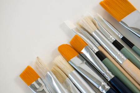 Various paintbrushes arranged in a row on white background Stock Photo