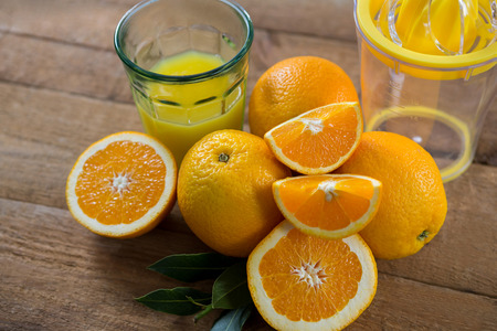 Close-up of oranges with glasses of juice and juicer on wooden table Stock Photo