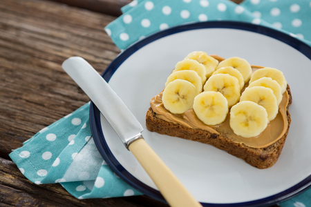 Sliced bananas spread on brown bread in plate on wooden table Stock Photo