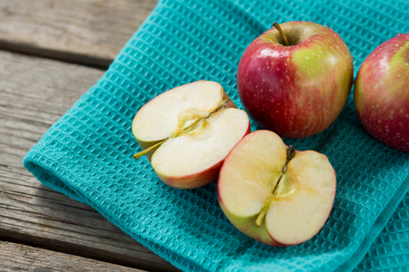Close-up of red halved apples kept on cloth on wooden table Stock Photo