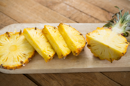 Slices and halved pineapple kept on chopping board on wooden table