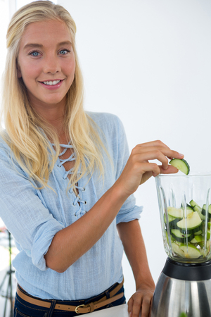 Woman preparing vegetable smoothie against white background