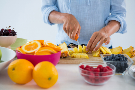 Mid-section of woman cutting fruits on chopping board against white background