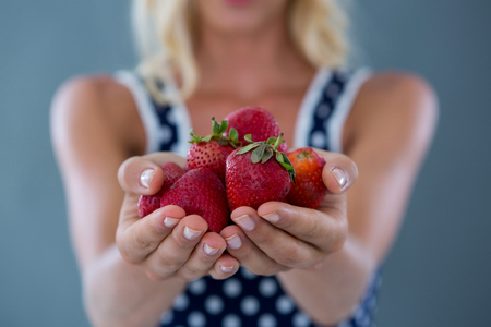 cupped: Mid-section of woman holding strawberries against grey background