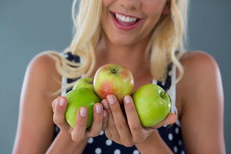 Beautiful woman holding green apples against grey background Stock Photo