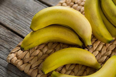 Close-up of bananas kept on placemat on wooden table