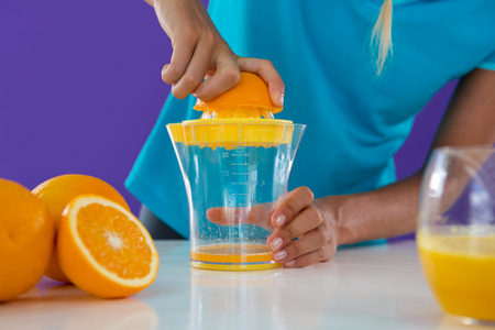 Mid-section of woman preparing orange juice from juicer against violet background Stock Photo
