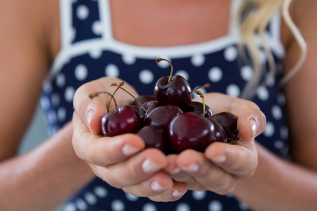 cupped: Mid-section of woman holding cherries Stock Photo