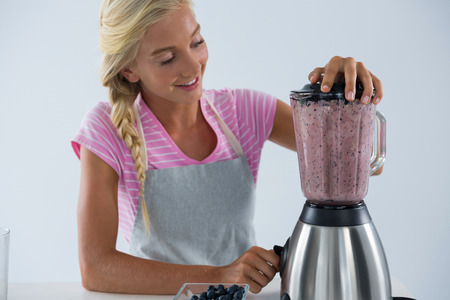 Woman preparing smoothie against white background