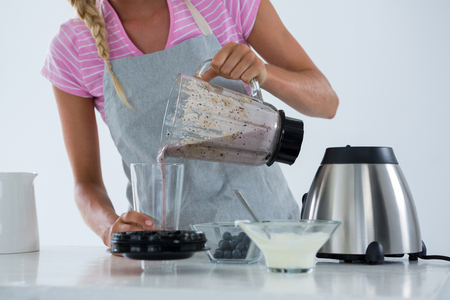 Woman pouring smoothie into glass at counter in kitchen