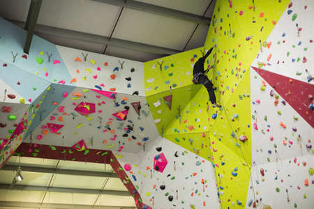 clambering: Man practicing rock climbing on artificial climbing wall in gym