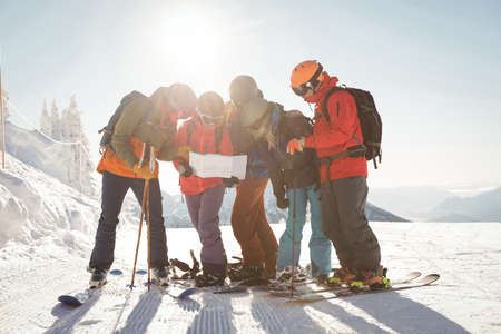 Group of skiers looking at map in snowy alps during winter LANG_EVOIMAGES