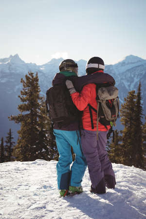 skiers: Rear view of two skiers standing together with arm around on snow covered mountain