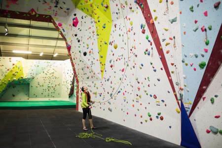 clambering: Trainer holding the rope near artificial climbing wall in gym