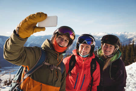 skiers: Three smiling female skiers taking selfie on mobile phone during winter