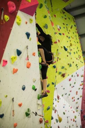 clambering: Woman practicing rock climbing on artificial climbing wall in gym