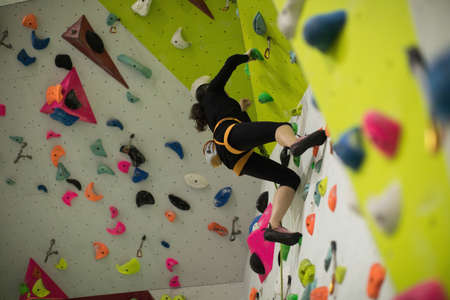 Woman practicing rock climbing on artificial climbing wall in gym