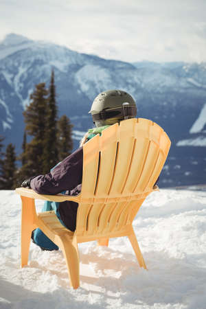 Rear view of woman sitting on chair at snow covered mountain against sky LANG_EVOIMAGES