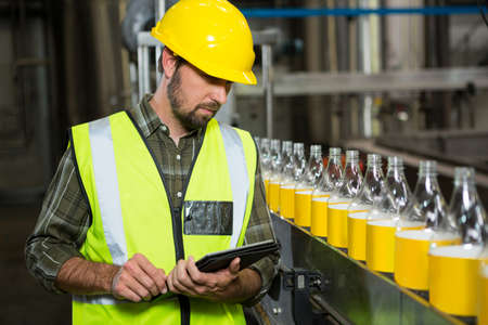 Serious male worker using digital tablet in juice factory LANG_EVOIMAGES