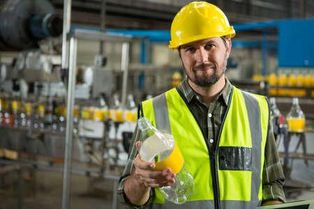 Portrait of confident male worker inspecting bottles in juice factory