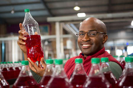 Portrait of smiling male worker showing juice bottle in factory
