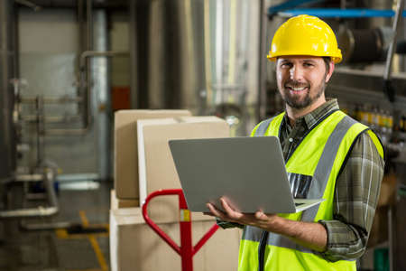Portrait of smiling male worker using laptop in distribution warehouse LANG_EVOIMAGES