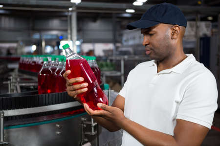 Young male worker inspecting juice bottle in factory LANG_EVOIMAGES