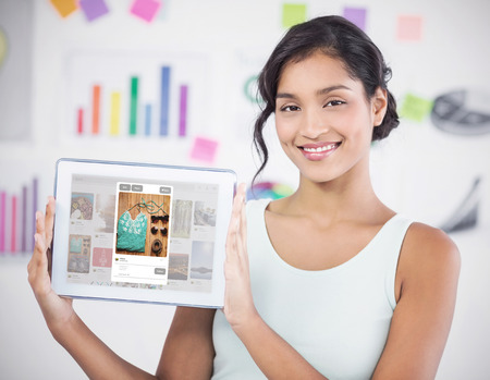Happy businesswoman showing digital tablet in creative office against composite image of website page blog