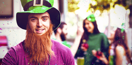 Flying colours against portrait of man celebrating st patricks day while holding beer glass 3d