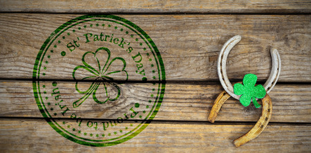 Composite image of St Patrick Day with flower symbol against horse shoe and shamrock Stok Fotoğraf