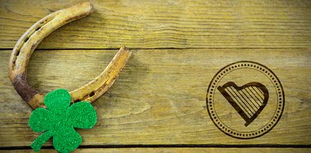 patrick's: Composite image of St Patrick Day with harp symbol against st patricks day shamrock with horseshoe Stock Photo