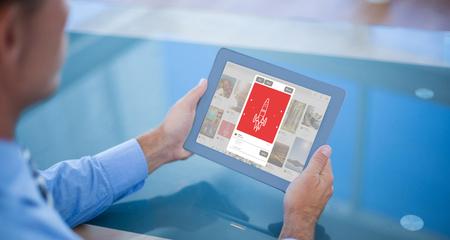 Businessman using his tablet  against composite image of rocket image on website