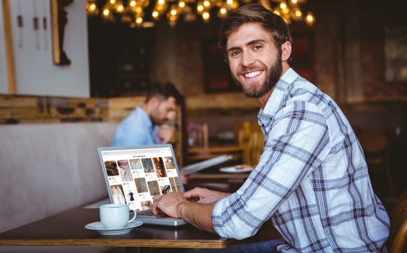 Composite image of website page against young man working on his computer
