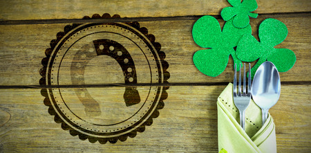 lucky charm: Composite image of St Patrick Day horseshoe symbol against st patricks day fork and spoon wrapped in napkin with shamrocks