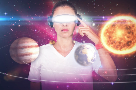 side viewing: Beautiful woman with virtual video glasses against composite image of solar system against white background 3d Stock Photo