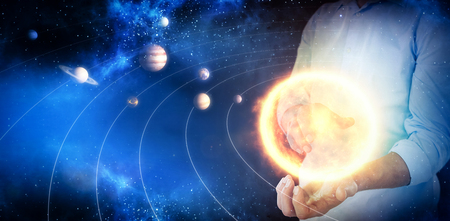 midsection: Midsection of man pretending to hold invisible object against graphic image of various planets with sun 3d