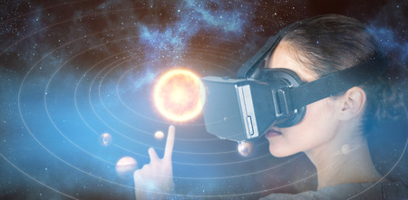 side viewing: Close up of woman gesturing while using virtual video glasses against graphic image of solar system 3d Stock Photo
