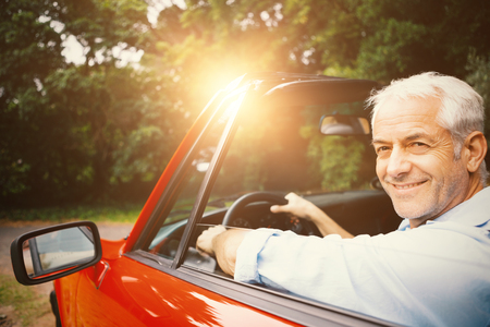 Smiling happy handsome man driving red car