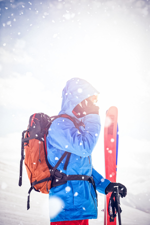 Side view of skier talking on mobile phone