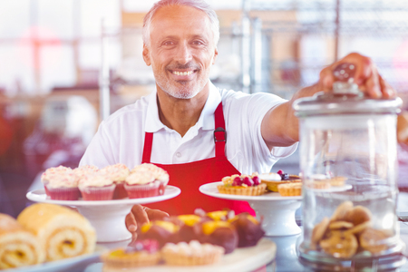 Graphic image of flare against portrait of happy barista behind plates of cakes