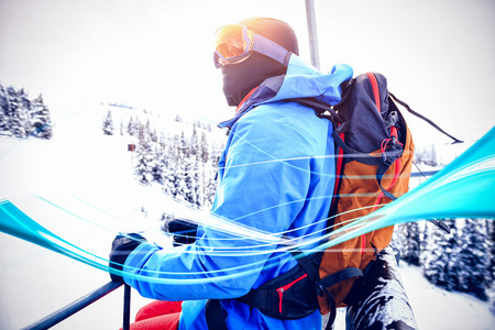 Blue wave design against skier looking at snow-covered mountains