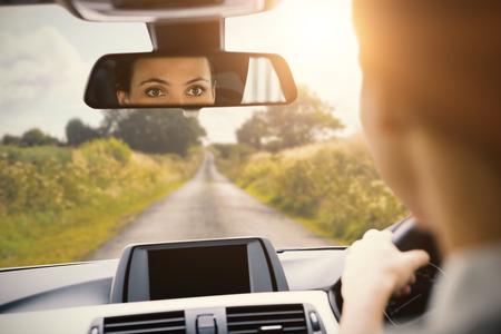 Vrouw rijdt met haar reflectie in de spiegel in haar auto