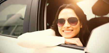 Portrait of smiling woman wearing sunglasses in her car