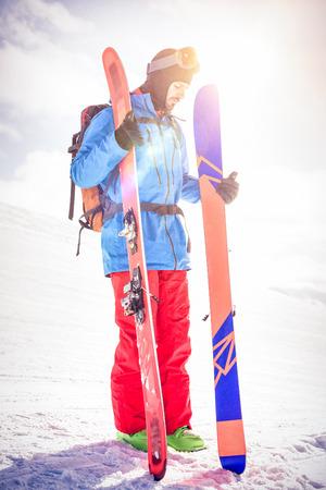 Full length skier holding ski on snowy mountains