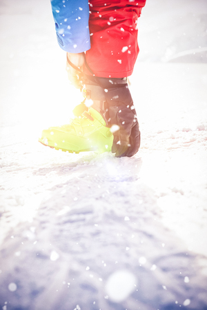 Low section of skier tying his boot strap