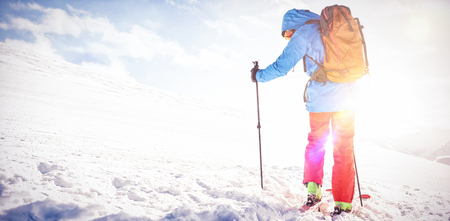 Full length rear view of skier walking on slope with ski Stock Photo