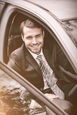 drivers seat: Portrait of smiling businessman sitting in drivers seat in his car