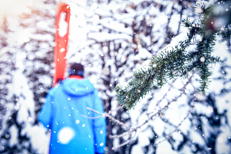 White background with vignette against skier walking with ski on snow covered forest Stock Photo
